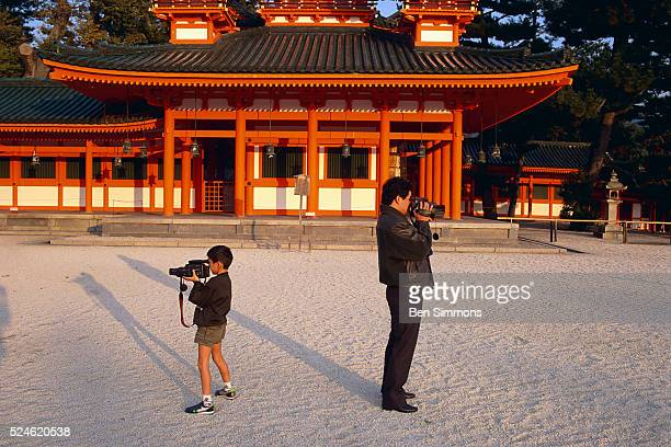 Father and son video tape in opposite directions at Heian Shrine during Children's Day in Kyoto Japan