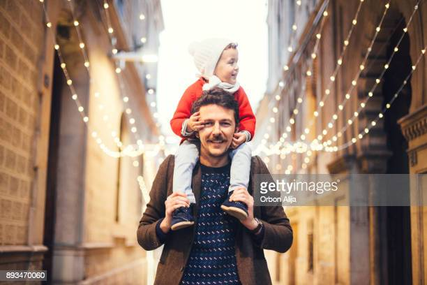 father and son wacthing the christmas lights - christmas scenes stock photos and pictures