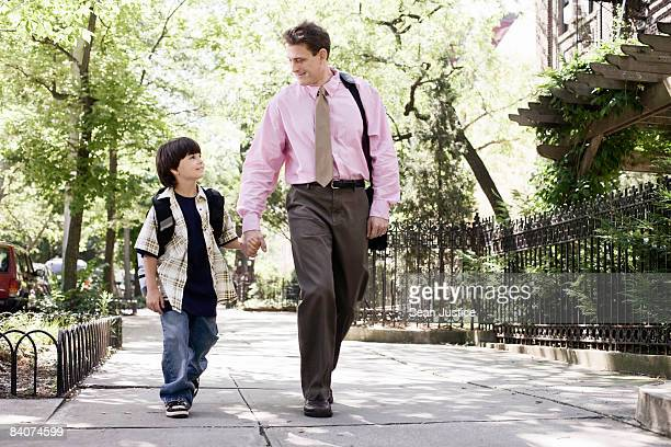 Father and son waling to work and school.