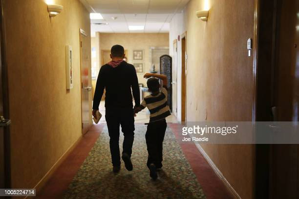 A father and son walk together as they are cared for in an Annunciation House facility after they were reunited with each other on July 25 2018 in El...