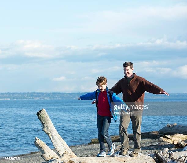 Father and son walking across tree trunk at coast