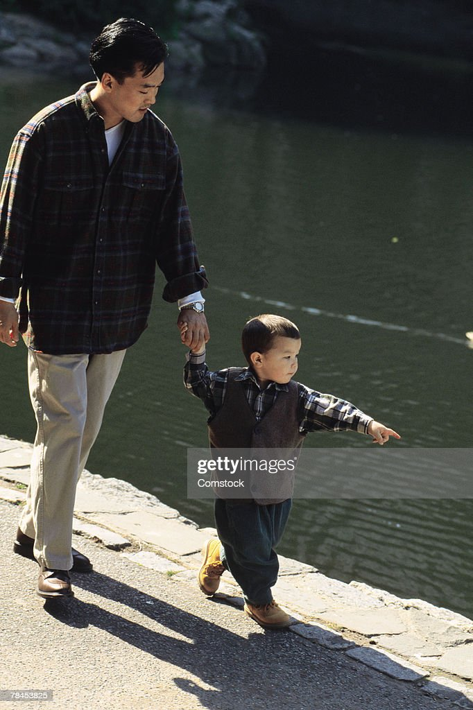 Father and son walking alongside a lake : Stockfoto