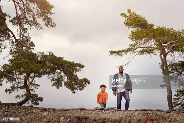 Father and son walking amidst trees against sky