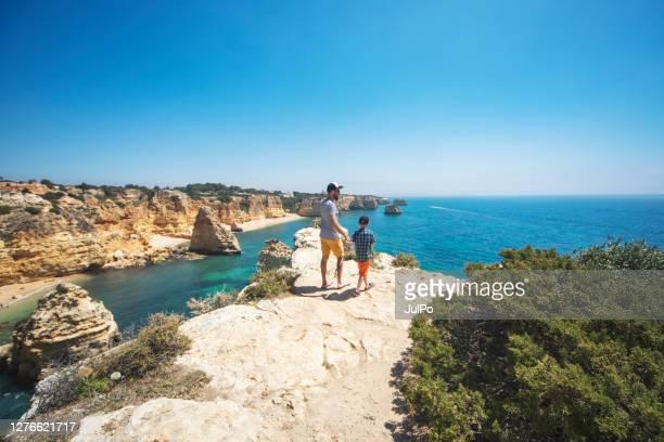 père et fils marchant à la plage - portugal photos et images de collection