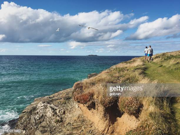 father and son walking dog at the coast path in harlyn bay, north coast of cornwall, england - coastline stock pictures, royalty-free photos & images