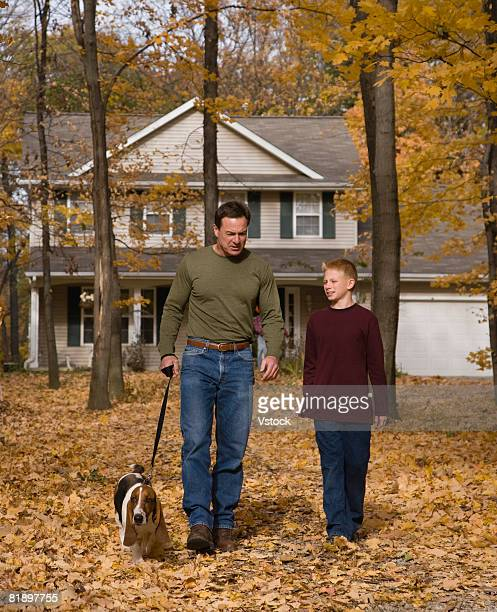 Father and son walking dog in woods