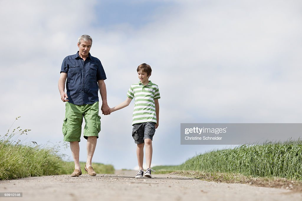Father and son walking down a road : Stock Photo