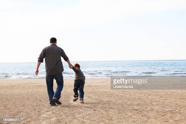 Father and son walking hand-in-hand on the sandy beach