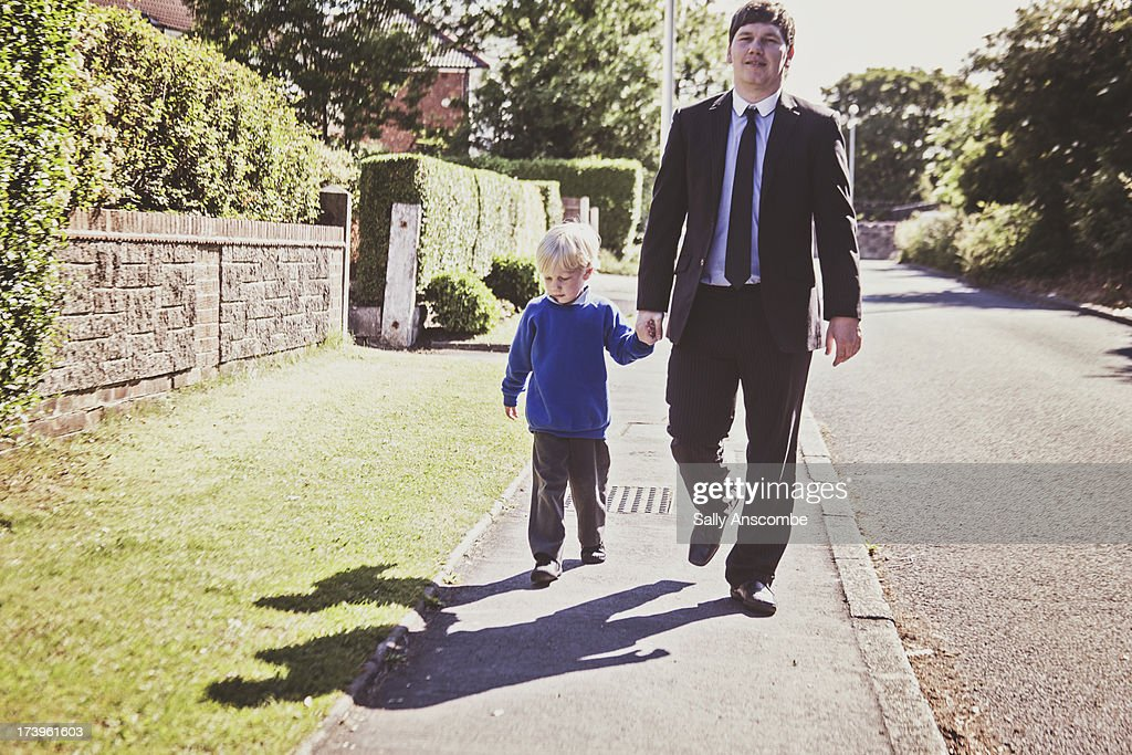 Father and son walking home from school : Stock Photo