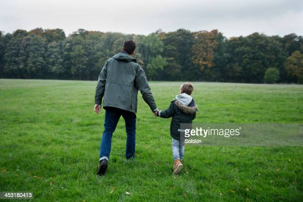 father and son walking in nature, holding hands - jacke stock-fotos und bilder