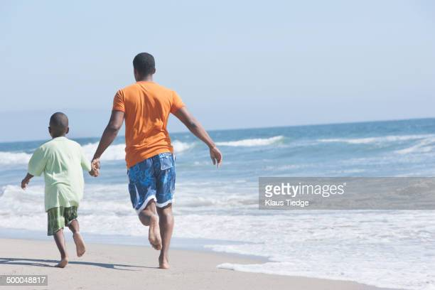 Father and son walking in waves on beach