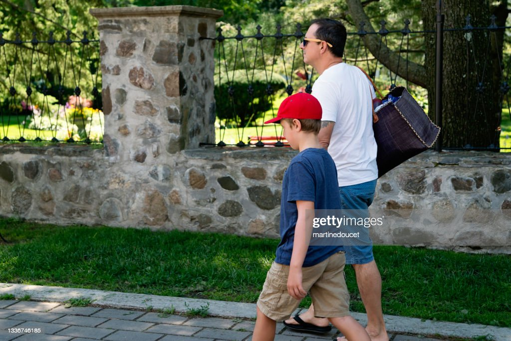 Father and son walking on a suburb street. : Stock Photo
