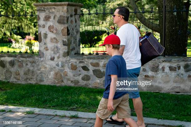 """father and son walking on a suburb street. - """"martine doucet"""" or martinedoucet stock pictures, royalty-free photos & images"""