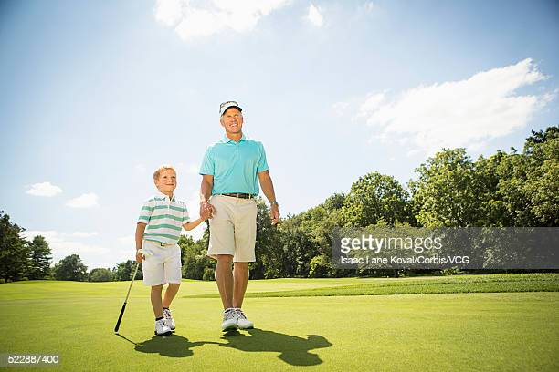 Father and son (6-7) walking on golf course