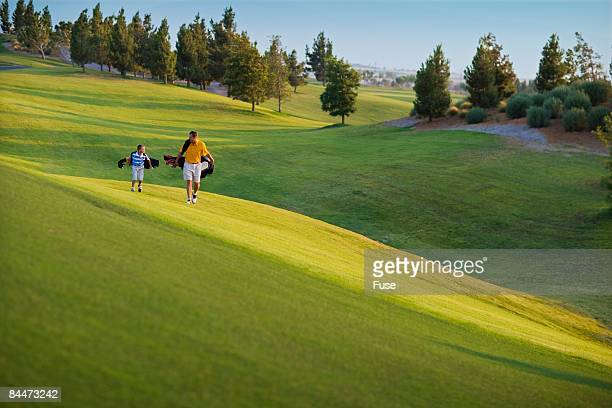 Father and Son Walking on Golf Course