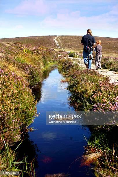father and son walking on mountain path - catherine macbride fotografías e imágenes de stock