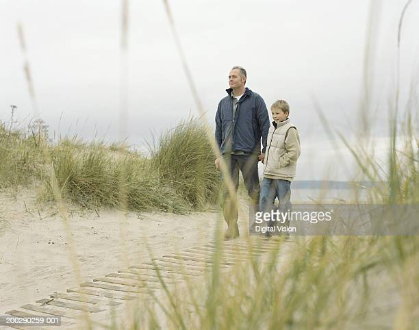 Father and son (8-10) walking on path by beach