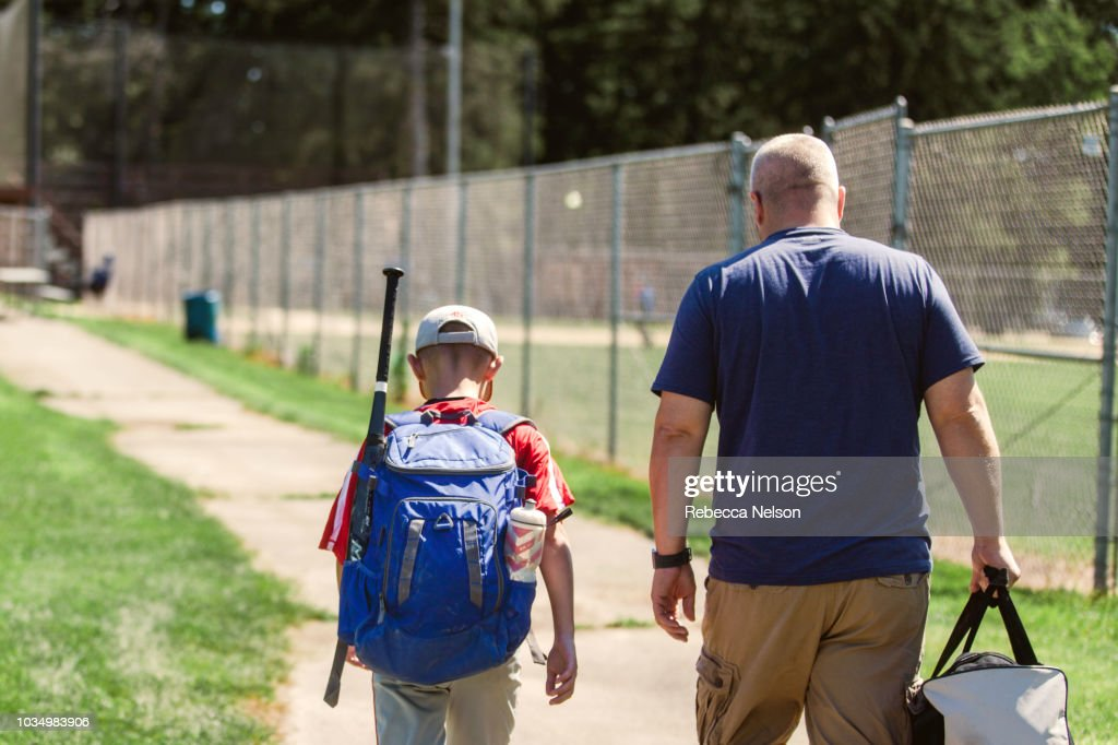 father and son walking on paved path to baseball diamond carrying baseball equipment : Stock Photo