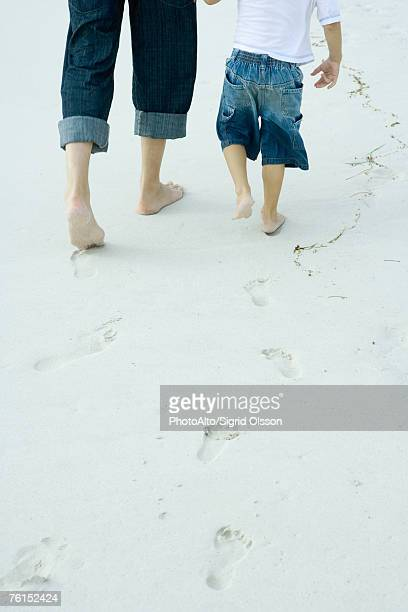 'Father and son walking on sand, low section, rear view'