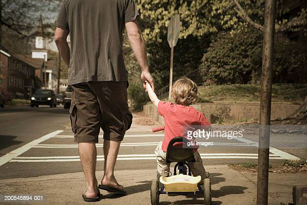 Father and son (2-4) walking on street, boy riding  bicycle, rear view