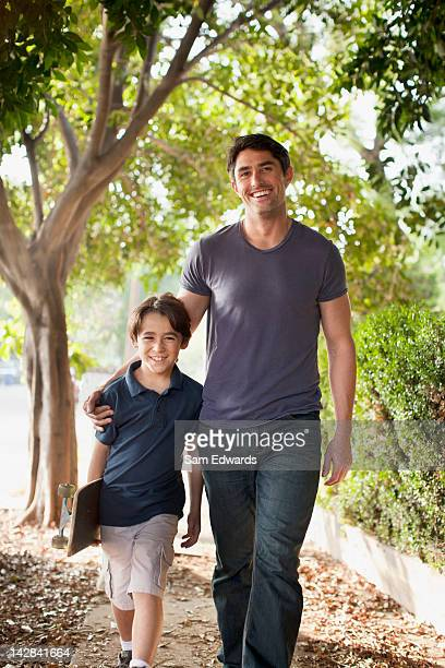 Father and son walking on suburban street