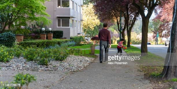father and son walking on the quiet city street in vancouver, bc, canada. - district stock pictures, royalty-free photos & images