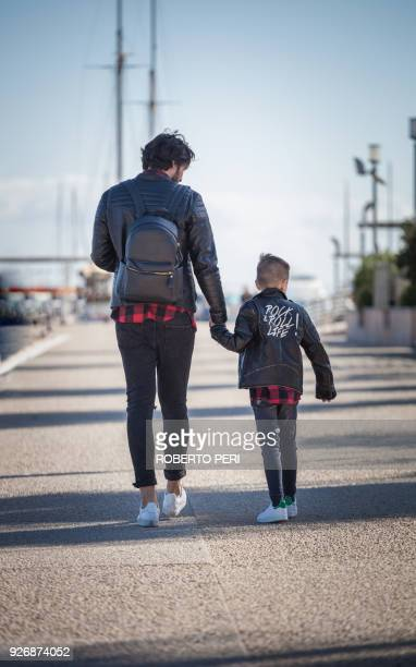 Father and son walking outdoors, holding hands, rear view