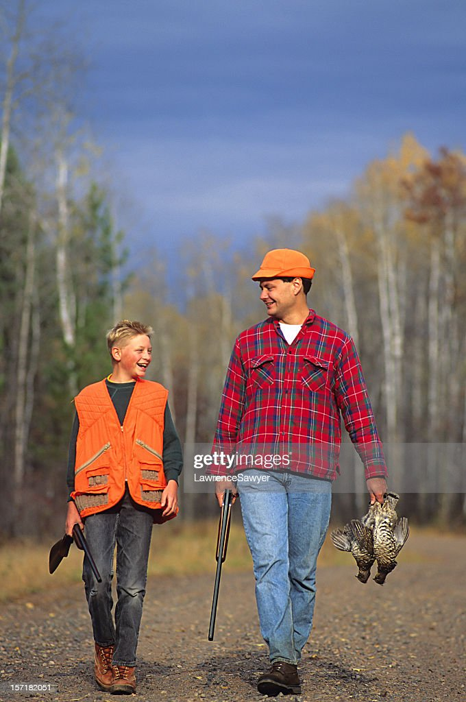 Father and son walking outdoors in hunting gear  : Stock Photo