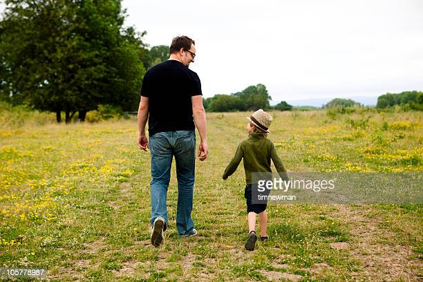 Father and son walking through a field.