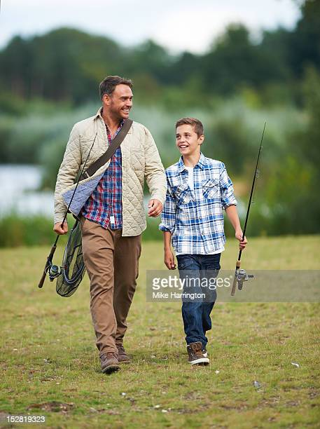 Father and son walking with fishing rods.
