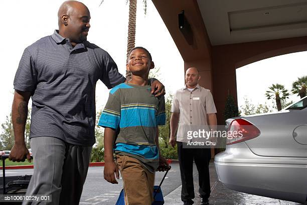 father and son (6-7 years) walking with suitcases through hotel driveway, low angle view - 25 29 years stock pictures, royalty-free photos & images