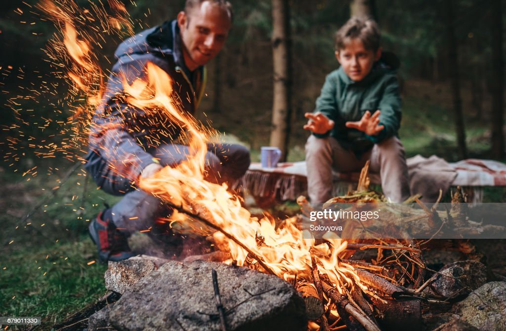 Father and son warms near campfire in forest : Stock Photo