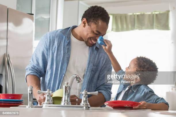 Father and son washing dishes in kitchen
