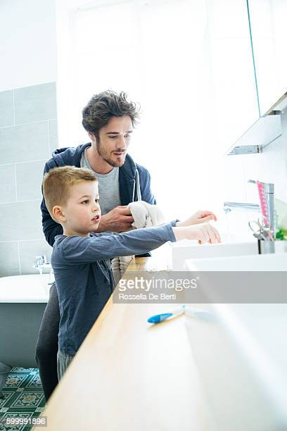 father and son washing hands together - kin in de hand stock pictures, royalty-free photos & images