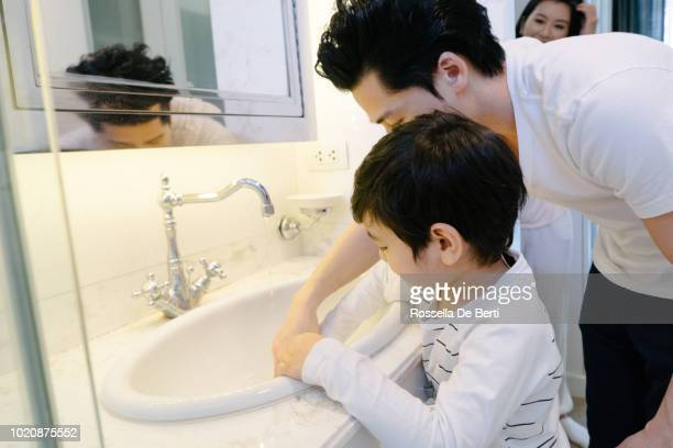 father and son washing hands with soap in bathroom - kin in de hand stock pictures, royalty-free photos & images