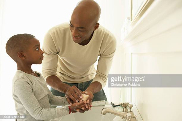 Father and son (5-7) washing hands with soap in bathroom, smiling