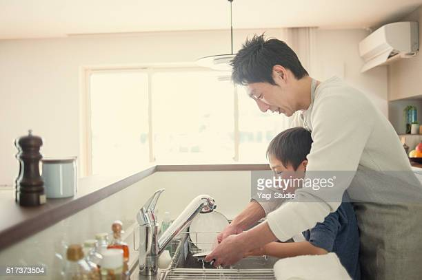 Father and son washing the dishes together in the kitchen