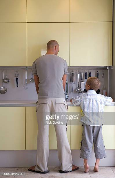 Father and son (5-7) washing up at kitchen sink, rear view