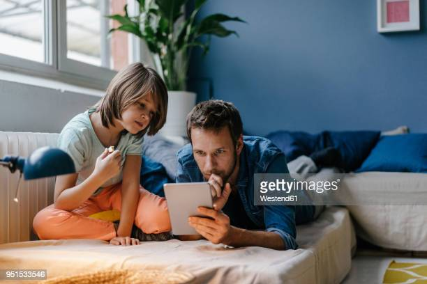 father and son watching a movie on tablet at home - arts culture and entertainment stock pictures, royalty-free photos & images