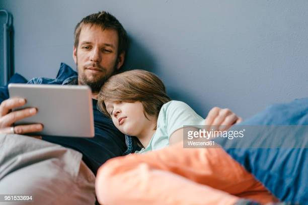 father and son watching a movie on tablet at home - mood stream stock pictures, royalty-free photos & images