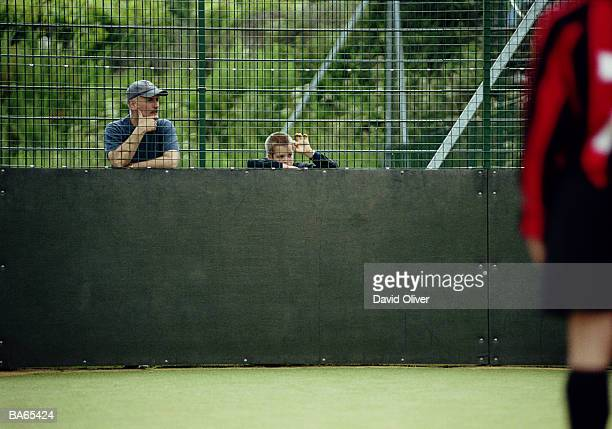 Father and son (6-8) watching football game through fence