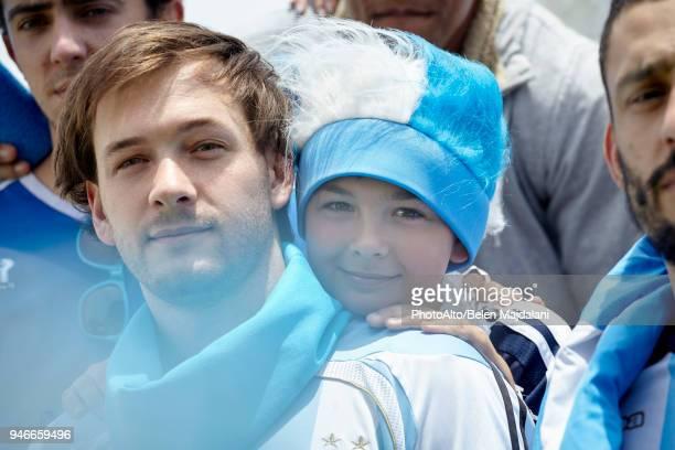 father and son watching football match, portrait - kopfbedeckung stock-fotos und bilder