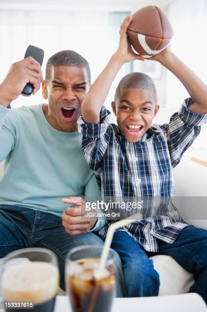 Father and son watching football on television