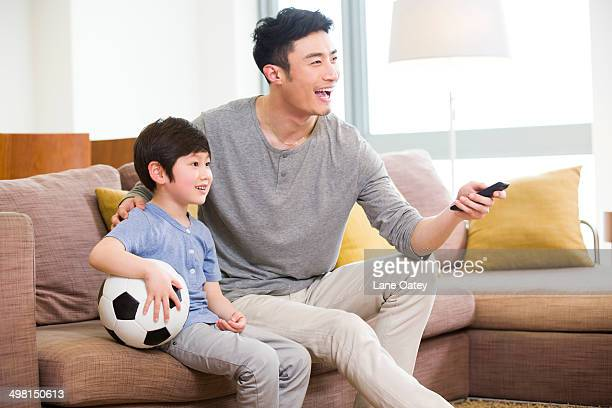 Father and son watching football on TV