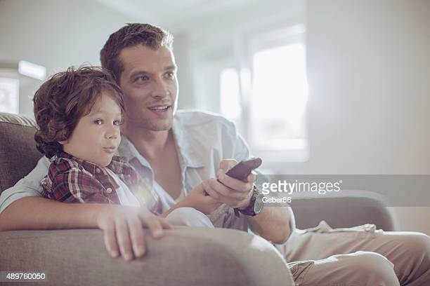 father and son watching football - family watching tv stock pictures, royalty-free photos & images