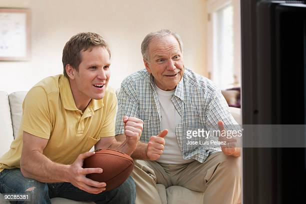Father and son watching football