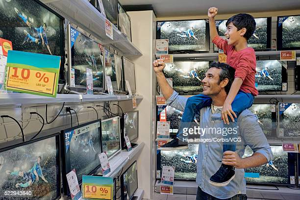 Father and son watching soccer game in electronics store