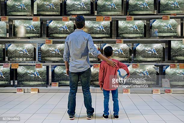 Father and son watching soccer in electronics store
