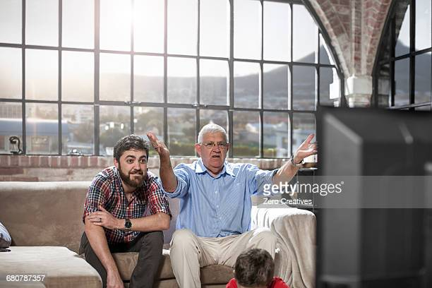 father and son watching television at home - disappointment stock pictures, royalty-free photos & images