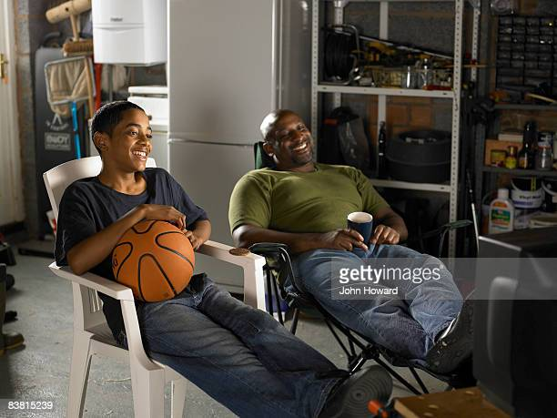 Father and Son watching TV in garage